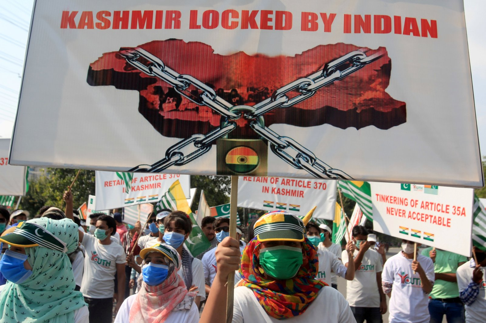 """People carry signs as they mark the """"Day of Exploitation in Kashmir"""" one year after the Indian government split the state of Jammu and Kashmir into two federally controlled territories and took away its special privileges, during a march in Lahore, Pakistan, Aug. 5, 2020. (Reuters Photo)"""