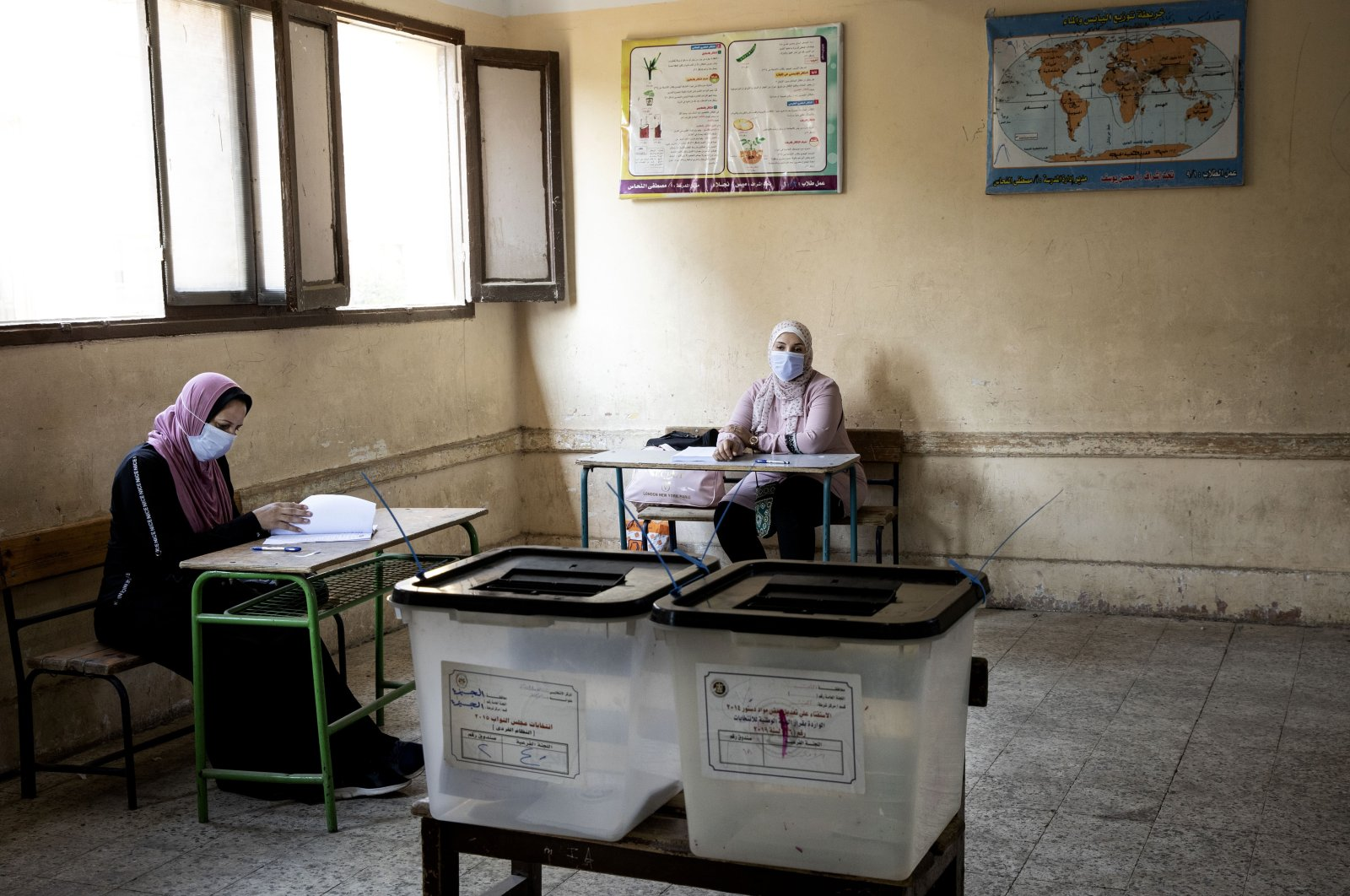 Election officials wait for people to vote on the first day of the Senate elections inside a polling station in Cairo, Egypt, Aug. 10, 2020. (AP Photo)
