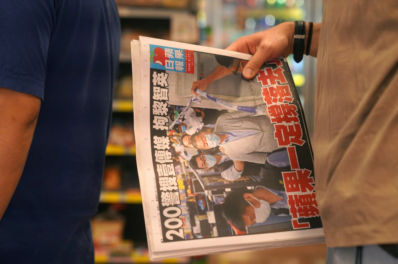 """A man waits to pay for an Apple Daily newspaper with the headline """"Apple Daily will fight on"""" after media mogul and founder Lai Chee-Ying, aka Jimmy Lai, was arrested by the national security unit inside a convenience store in Hong Kong, China, Aug. 11, 2020. (Reuters Photo)"""