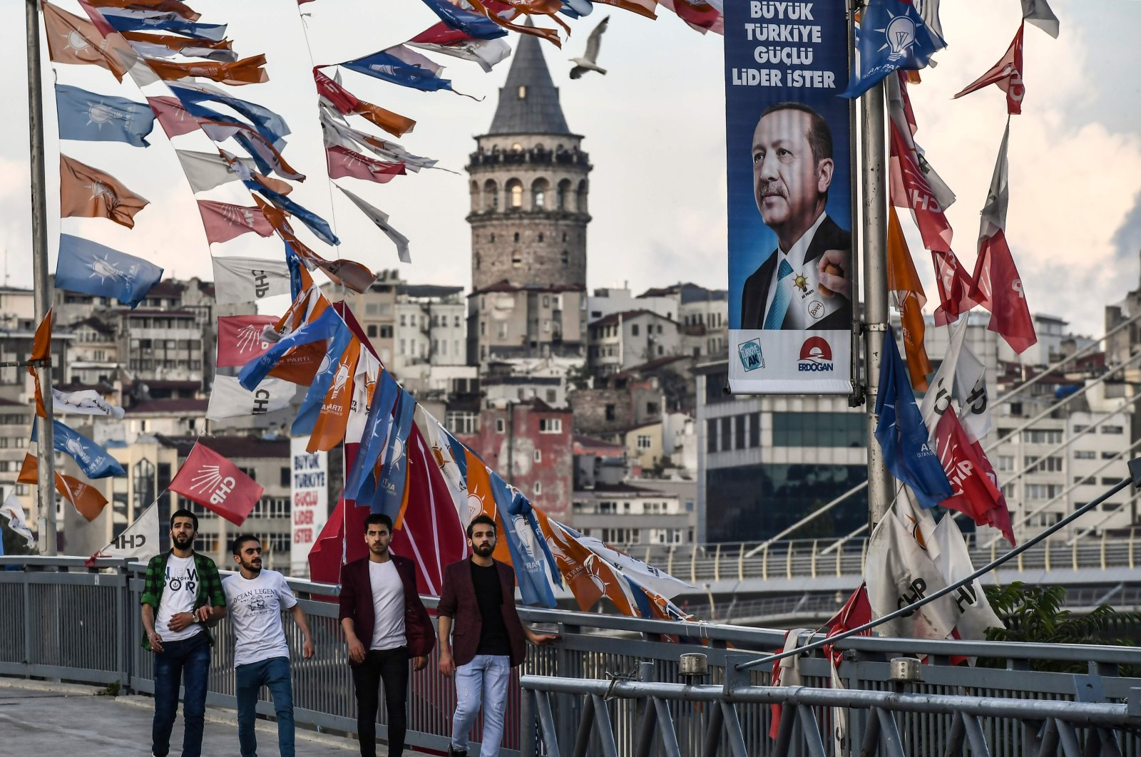 People pass by banners with the portrait of President Erdoğan in Istanbul, June 18, 2018. (AFP)