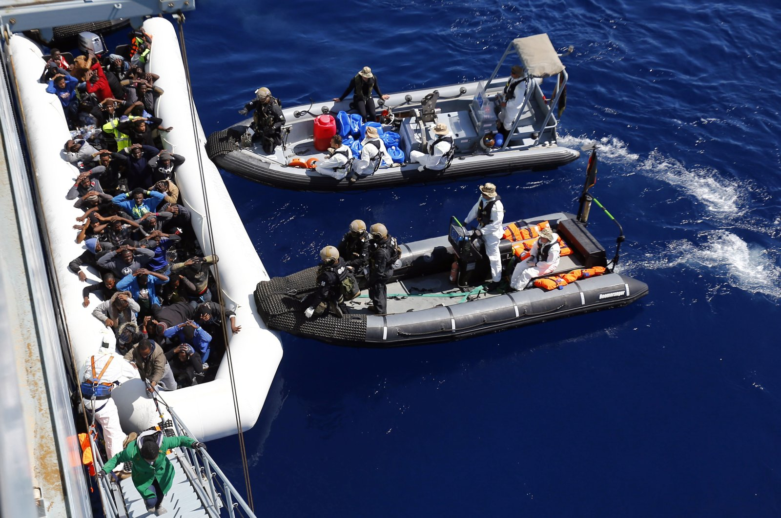 German navy sailors and Finland's special navy forces help migrants to board the German combat supply ship during the EU's Operation Sophia in the Mediterranean Sea off the coast of Libya, March 29, 2016.  (AP Photo)