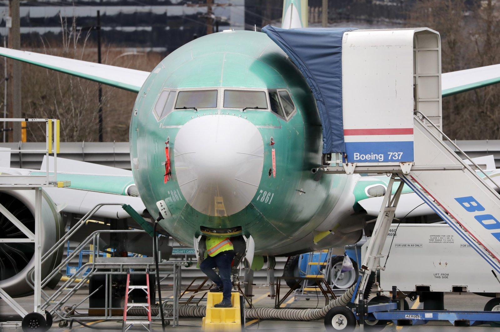 A worker looks up underneath a Boeing 737 Max jet, in Renton, Washington, U.S., Dec. 16, 2019. (AP Photo)