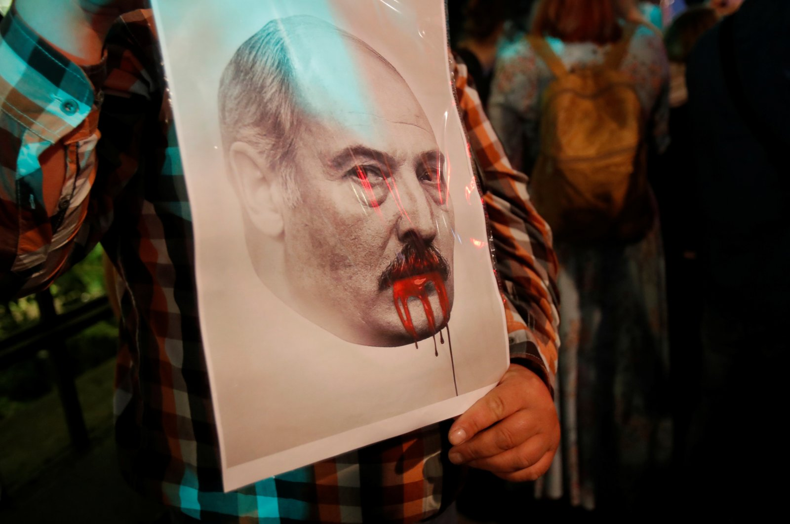 A demonstrator holds a portrait of Belarusian President Alexander Lukashenko during a protest against the presidential election preliminary results outside the Belarusian embassy in Moscow, Russia, Aug. 11, 2020. (Reuters Photo)