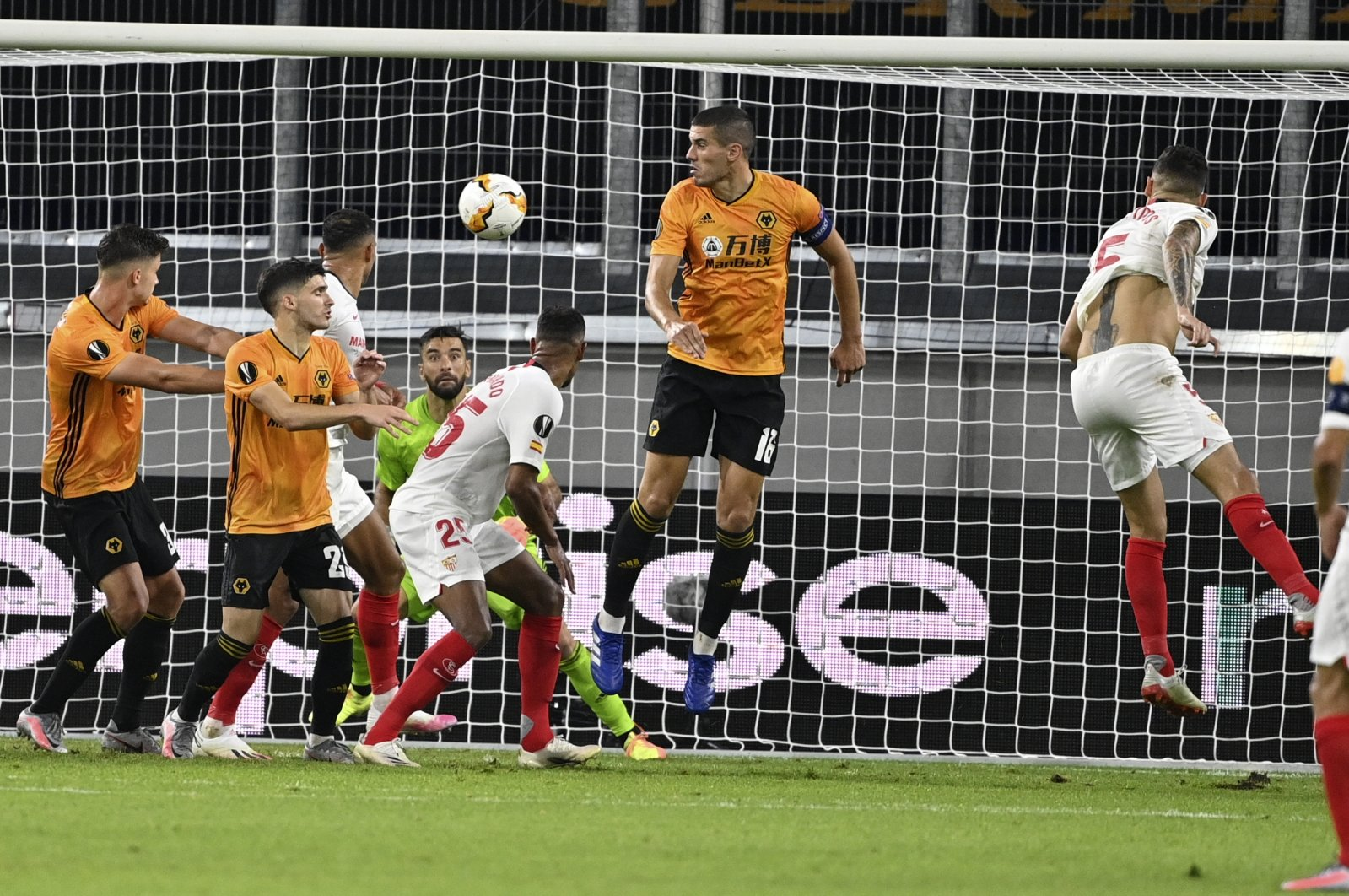 Sevilla's Lucas Ocampos, right, heads the ball to score his team's first goal during the Europa League quarterfinal match against Wolverhampton Wanderers in Duisburg, Germany, Aug. 11, 2020. (AP Photo)