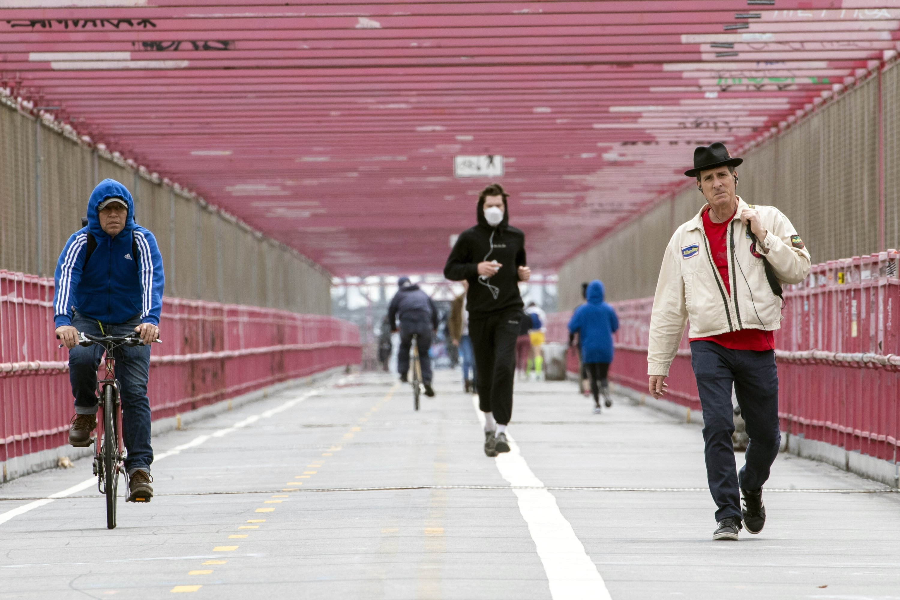 A jogger wearing a face mask runs in between a biker and a pedestrian not wearing masks as they make their way over the Williamsburg bridge in New York City, New York, U.S., May 11, 2020. (AP Photo)