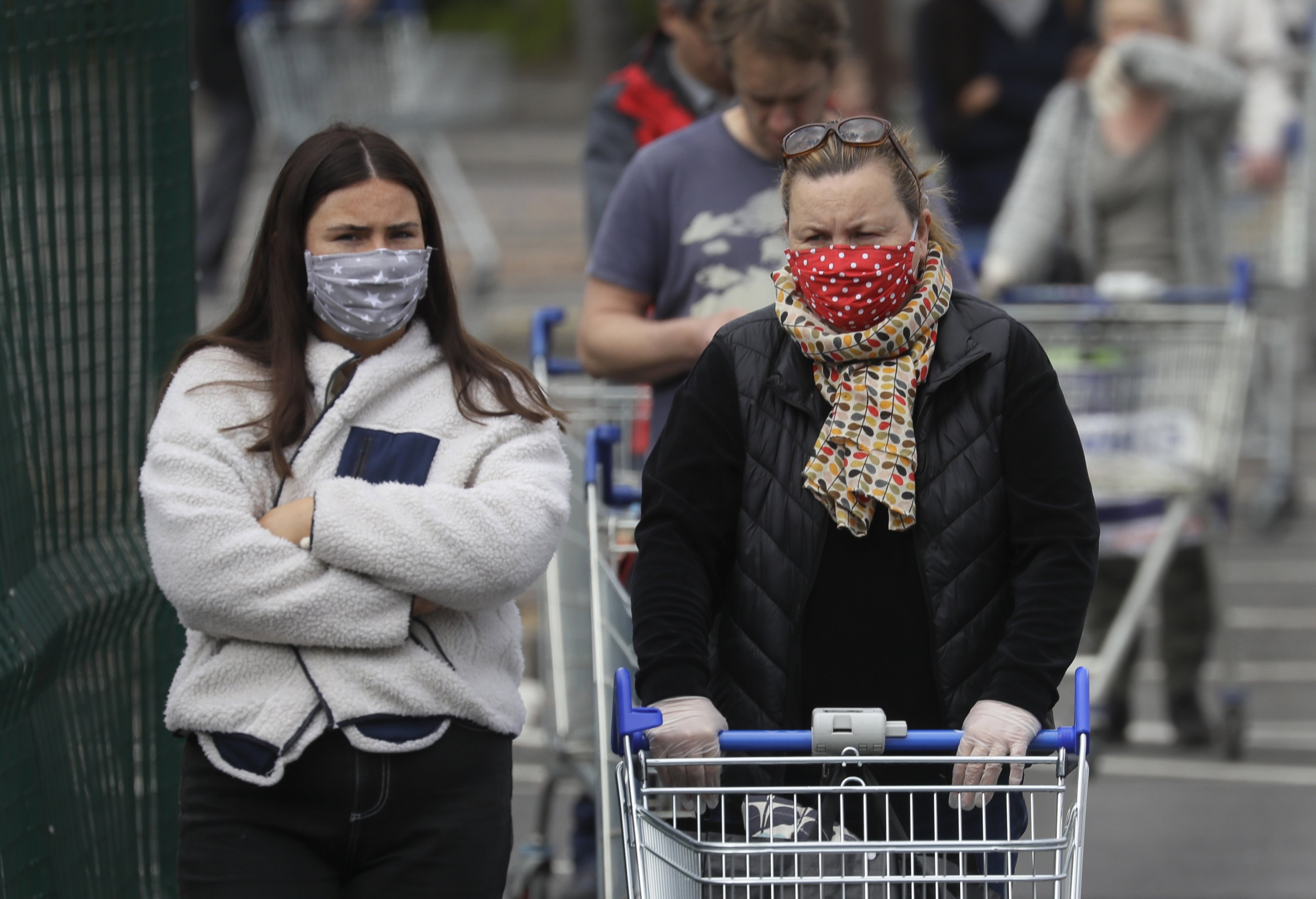 People wear face masks to protect against the coronavirus as they queue to enter a supermarket in London, April 29, 2020. (AP Photo)