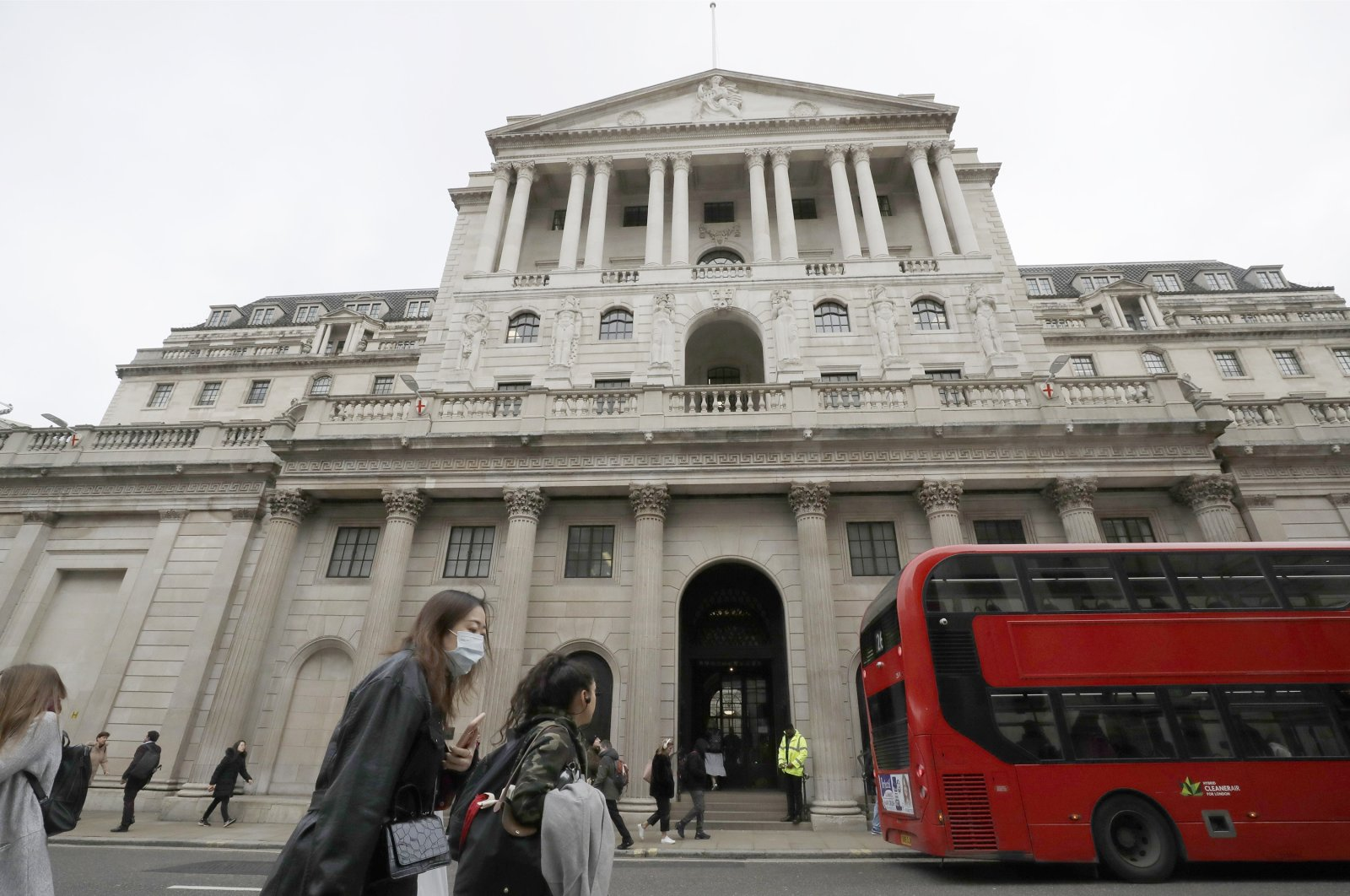 Pedestrians wearing face masks pass the Bank of England in London, Britain, March 11, 2020. (AP Photo)
