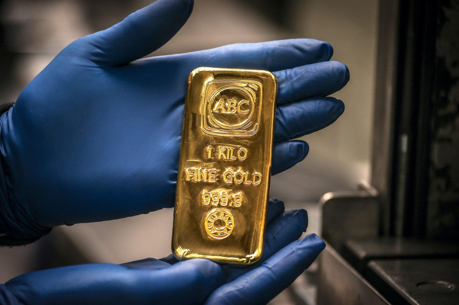 A worker displays a 1-kilogram gold bullion bar at the ABC Refinery in Sydney, Australia, Aug. 5, 2020. (AFP Photo)