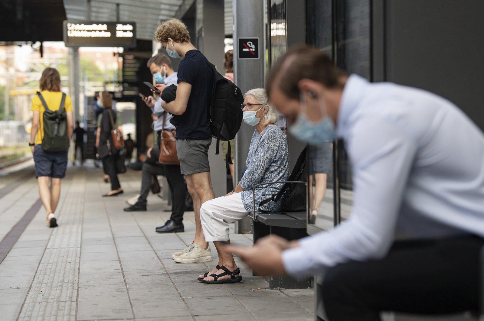 Passengers wear masks as they wait for a tram in Aarhus, Denmark, Aug. 10, 2020. (EPA-EFE Photo)