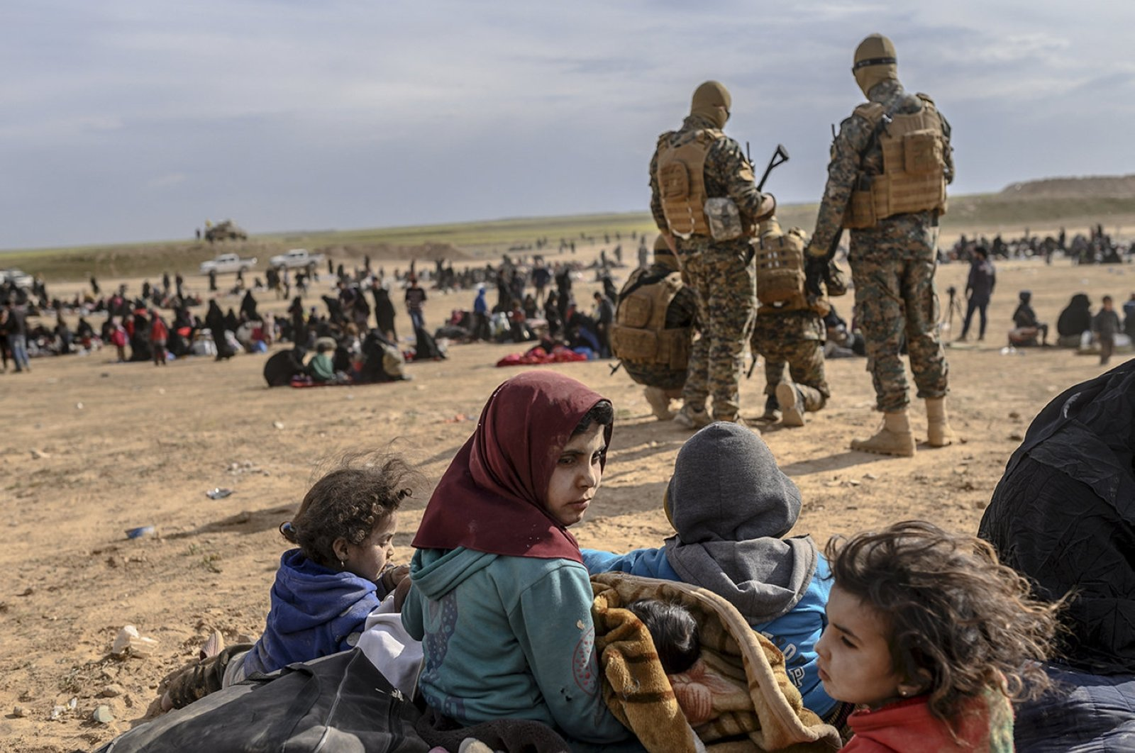 Civilians evacuated from the Daesh group's embattled holdout of Baghouz wait at a screening area held by U.S.-backed YPG/PKK terrorists, in the northeastern Syrian province of Deir el-Zour, March 5, 2019. (AFP File Photo)