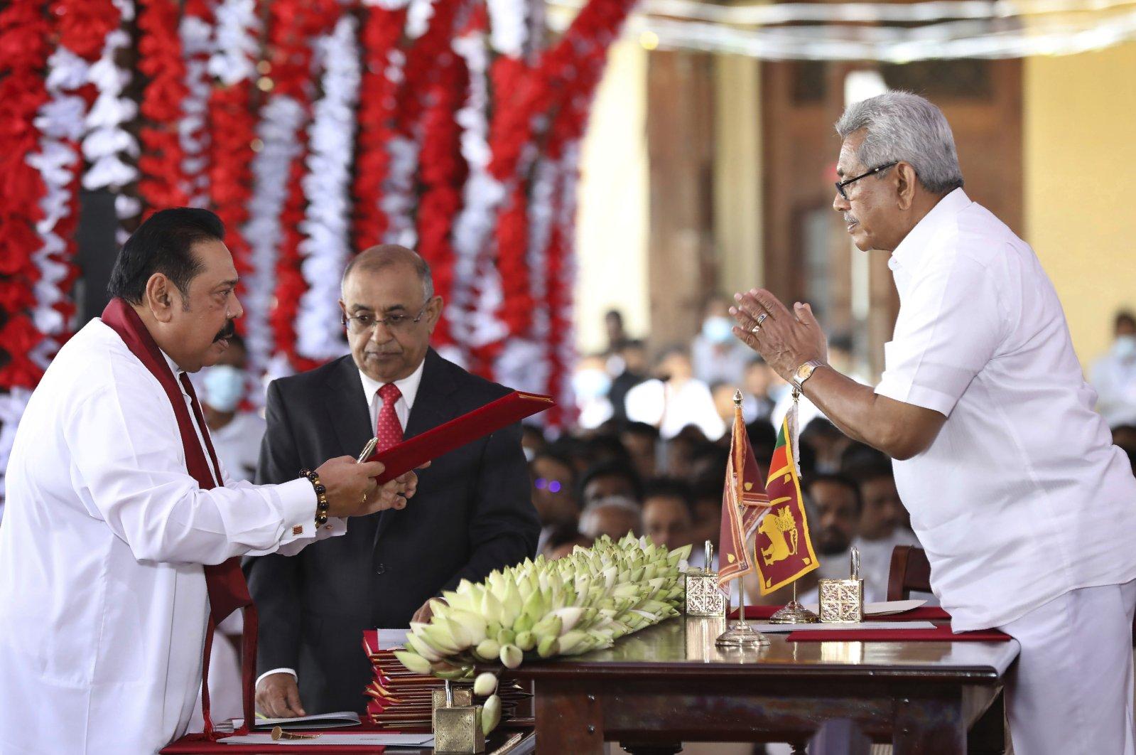 Sri Lankan President Gotabaya Rajapaksa (R) hands over credentials to his elder brother, Prime Minister Mahinda Rajapaksa during a ceremony, Kandy, Aug. 12, 2020. (AP Photo)