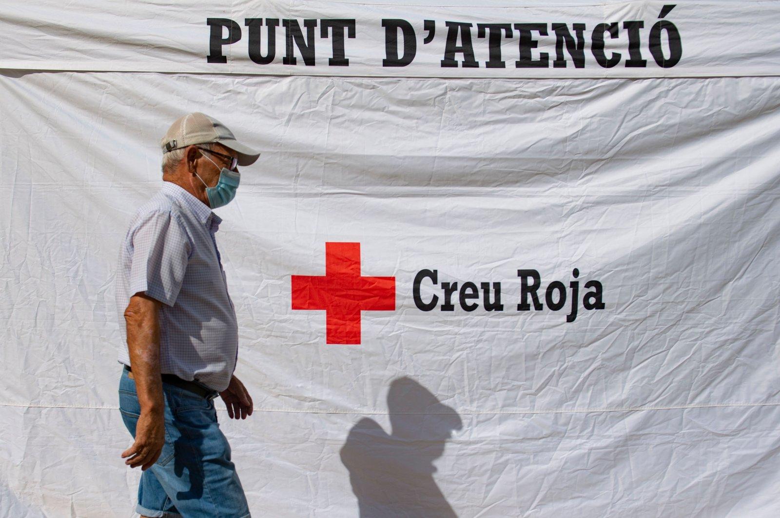 A man walks past a tent outside a medical center where people are tested for the novel coronavirus, Santa Coloma de Gramenet, Catalonia, Spain, Aug. 10, 2020. (AFP Photo)