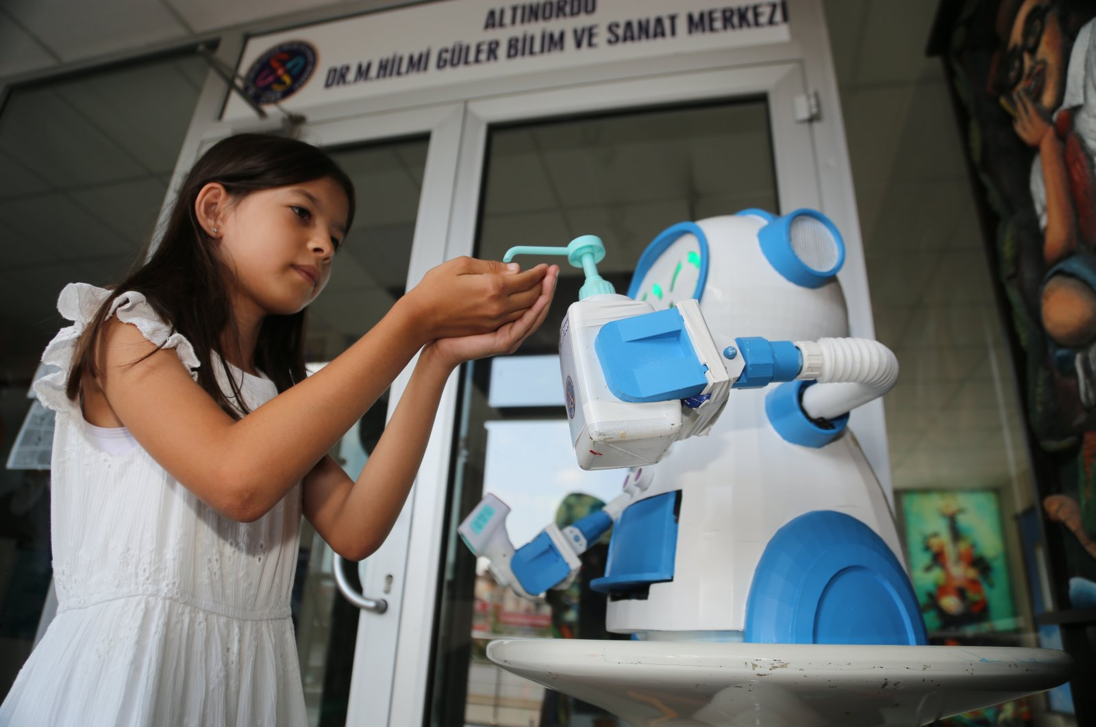 The robot pours disinfectant into the hand of a girl in Ordu, northern Turkey, Aug. 12, 2020. (AA Photo)