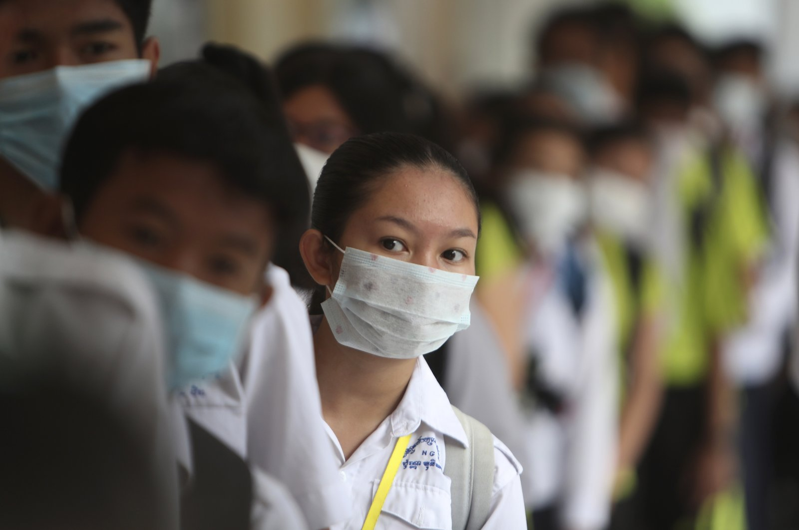 Students line up to sanitize their hands to avoid contact with the coronavirus before their morning class at a high school in Phnom Penh, Cambodia, Jan. 28, 2020. (AP Photo)