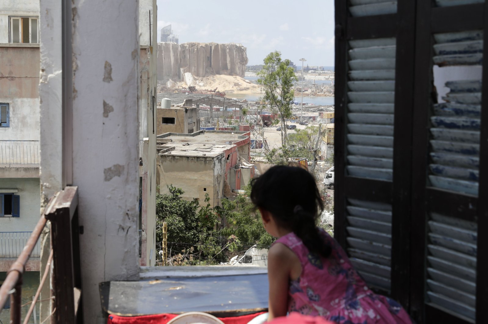 A girl stands at the window of her apartment overlooking the destroyed silo at the Port of Beirut following a huge chemical explosion that devastated large parts of the Lebanese capital last week, Aug. 11, 2020. (AFP Photo)