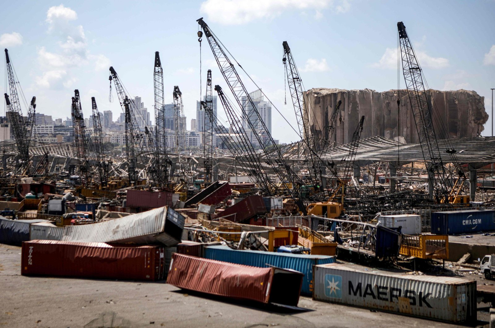 Destroyed freight containers sit under cranes against the backdrop of grain silos damaged in an explosion last week at the Port of Beirut in Lebanon's capital, Aug. 9, 2020. (AFP Photo)