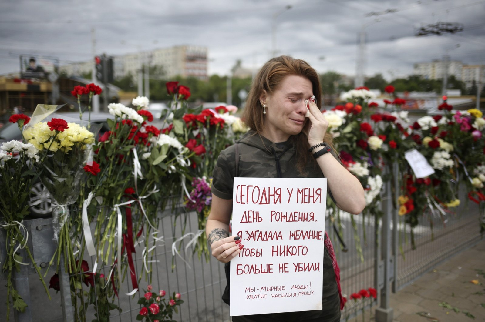 """Alina Krus, 26, holds a poster at the place where a protester died amid the clashes in Minsk, Belarus, Wednesday, Aug. 12, 2020 saying """"It's my birthday today. I made a wish that no one gets killed. We are peaceful people. Enough with the violence, please."""" (AP Photo)"""