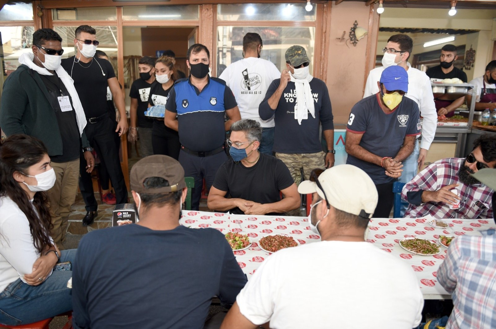 Bollywood star Aamir Khan, surrounded by his entourage, fans and officials, sits at a kebab restaurant in Adana, southern Turkey, Aug. 12, 2020. (Seyhan Municipality via AA)