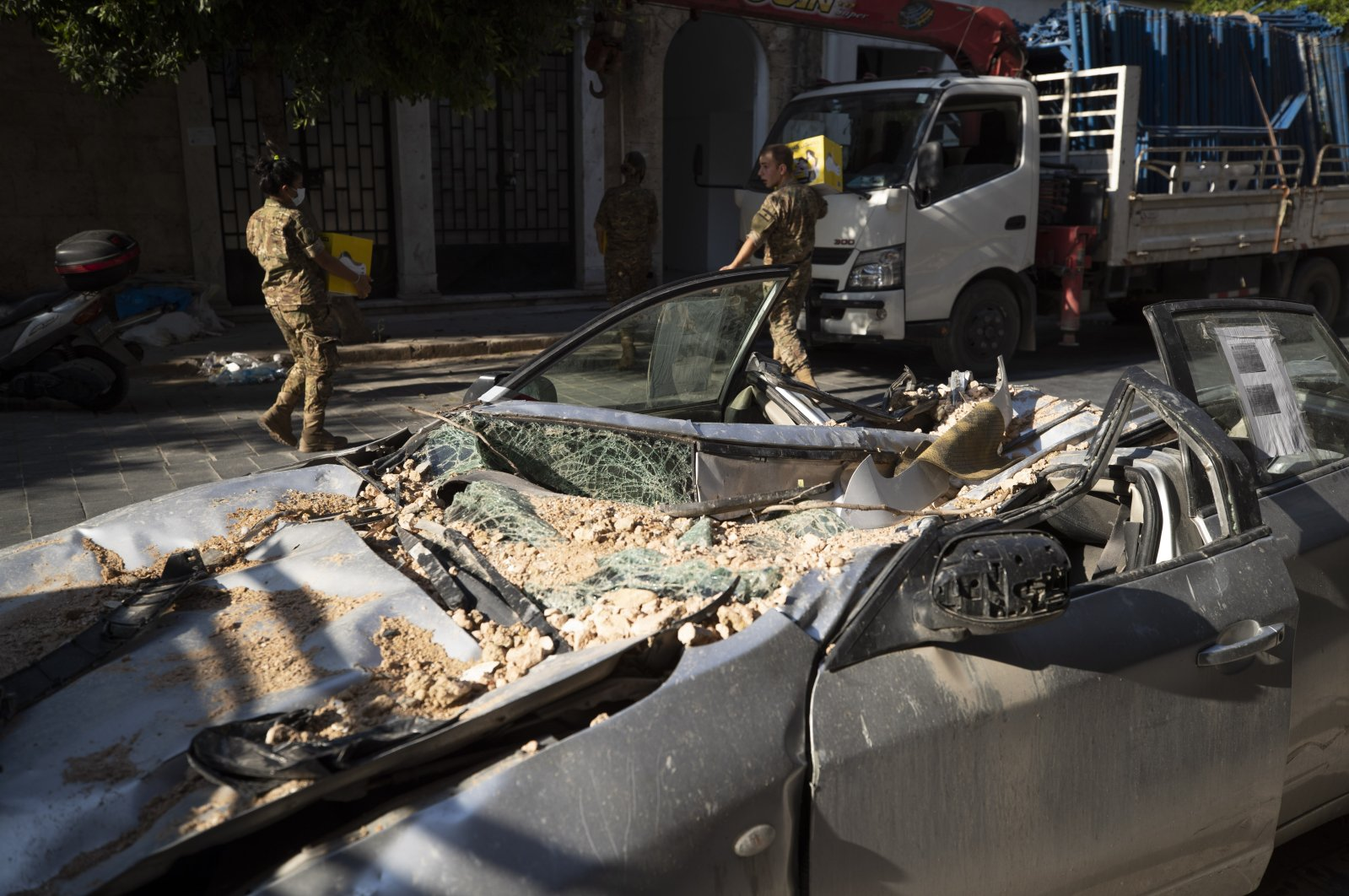 Lebanese Army soldiers carry aid boxes past a destroyed car near the scene of last week's explosion that hit the seaport of Beirut, Lebanon, Aug. 12, 2020. (AP Photo)