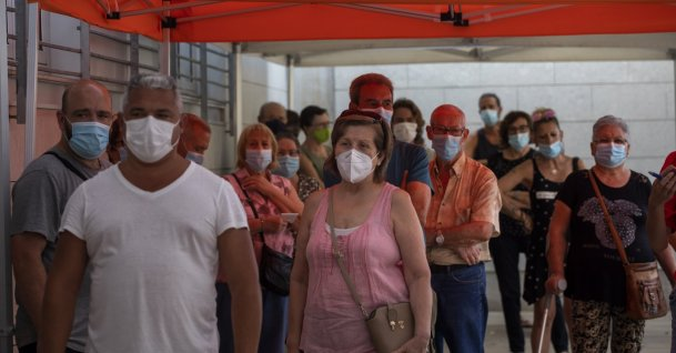 People wearing face masks queue up to be tested for COVID-19, outside a local clinic in Santa Coloma de Gramanet in Barcelona, Spain, Aug. 11, 2020. (AP Photo)