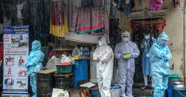 Health workers wearing personal protective equipment (PPE) suits take shelter while conducting a COVID-19 screening under heavy rain, Mumbai, India, Aug. 12, 2020. (AFP Photo)