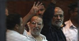 Muslim Brotherhood's Supreme Guide Mohamed Badie (R) and Muslim Brotherhood leader Essam El-Erian (C) gesture during their trial at a court in Cairo, Egypt, Aug. 30, 2014. (Reuters Photo)