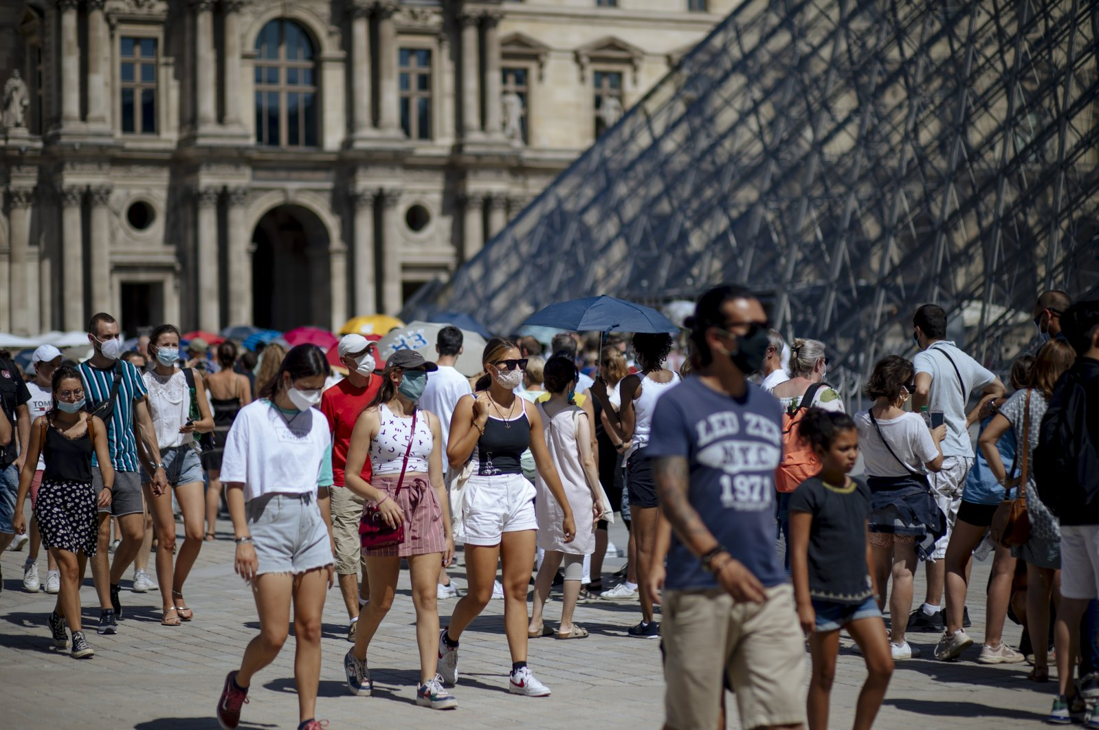 People walk past the Louvre Museum in Paris, France, Aug. 12, 2020. (AP Photo)