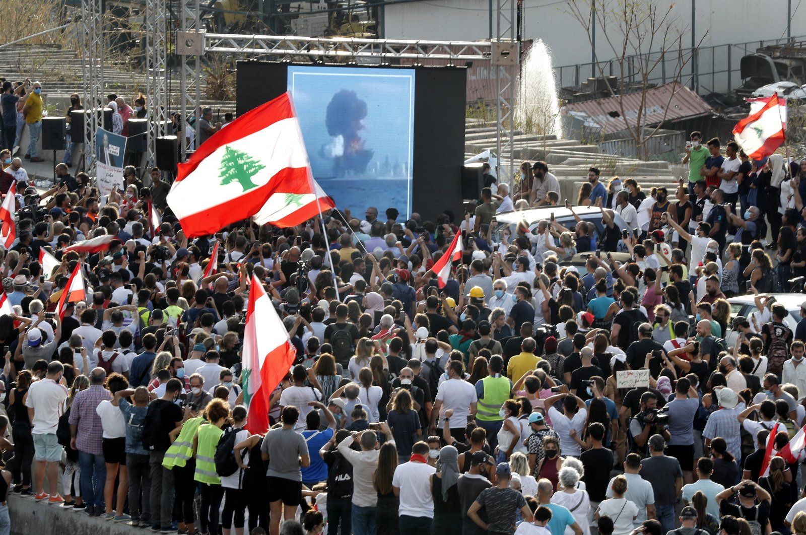 People watch on a giant screen the moment of the massive explosion, as they gather in honor of the victims killed or wounded in the Lebanese capital, in Beirut, Lebanon, Aug. 11, 2020.   (AP Photo)