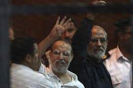 Muslim Brotherhood's Supreme Guide Mohamed Badie (R) and Muslim Brotherhood leader Essam El-Erian (C) gesture during their trial at a court in Cairo, Egypt, Aug. 30, 2014. (Reuters Photo)