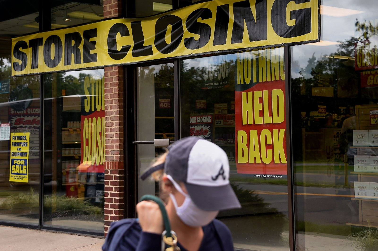 A woman walks past a store closing down due to the economic impact of the coronavirus pandemic, Arlington, Virginia, U.S., Aug. 4, 2020. (AFP Photo)