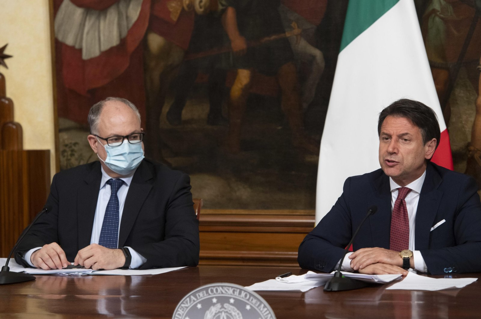 Italian Prime Minister, Giuseppe Conte (R), with Economy Minister Roberto Gualtieri (L), announces the latest set of measures under another emergency decree during the coronavirus pandemic in Rome, Italy on Aug. 7, 2020. (AP Photo)