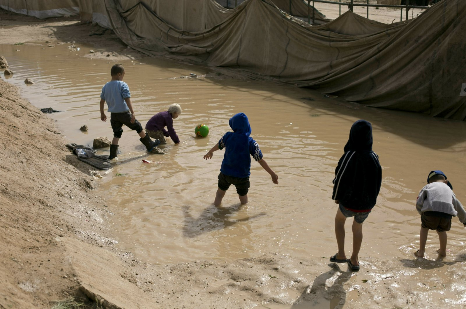 In this March 31, 2019 file photo, children play in a mud puddle in the section for foreign families at Al-Hol camp in Hasakeh province, Syria. (AP File Photo)