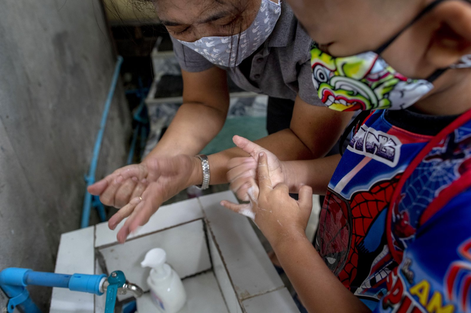 A teacher, left, guides a child on how to wash hands properly at the entrance of Makkasan preschool in Bangkok, Thailand, Wednesday, July 1, 2020. (AP Photo)