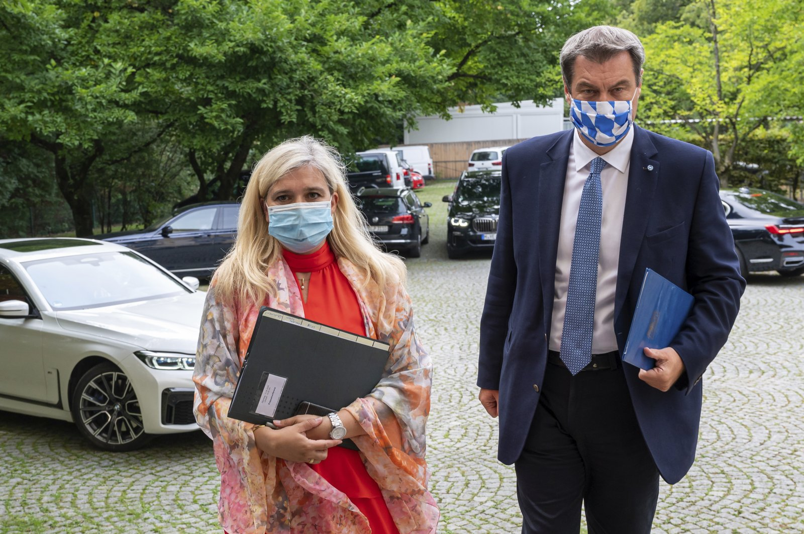 Melanie Huml, Health Minister of the German state of Bavaria, left, and Bavaria's premier Markus Soeder, right, arrive for a joint press conference in Munich, Germany, Thursday, Aug. 13, 2020. (AP Photo)