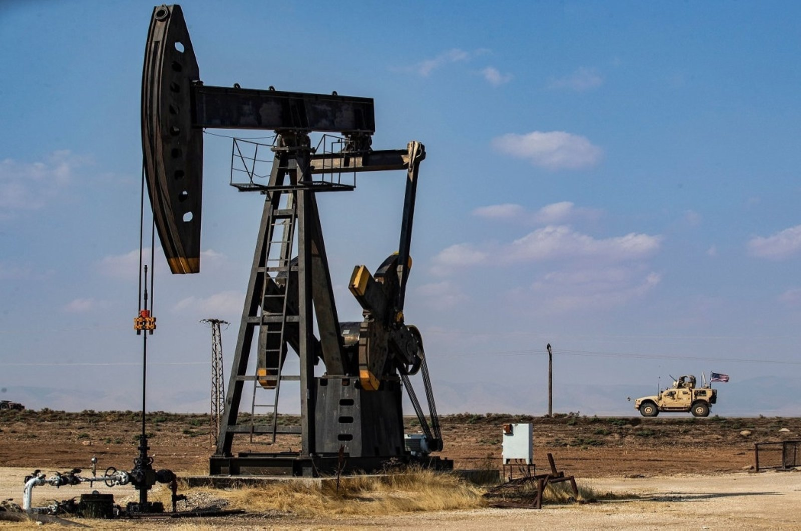 A U.S. military vehicle, part of a convoy arriving from northern Iraq, drives past an oil pump jack in the countryside of Syria's northeastern city of Qamishli on Oct. 26, 2019. (AFP Photo)