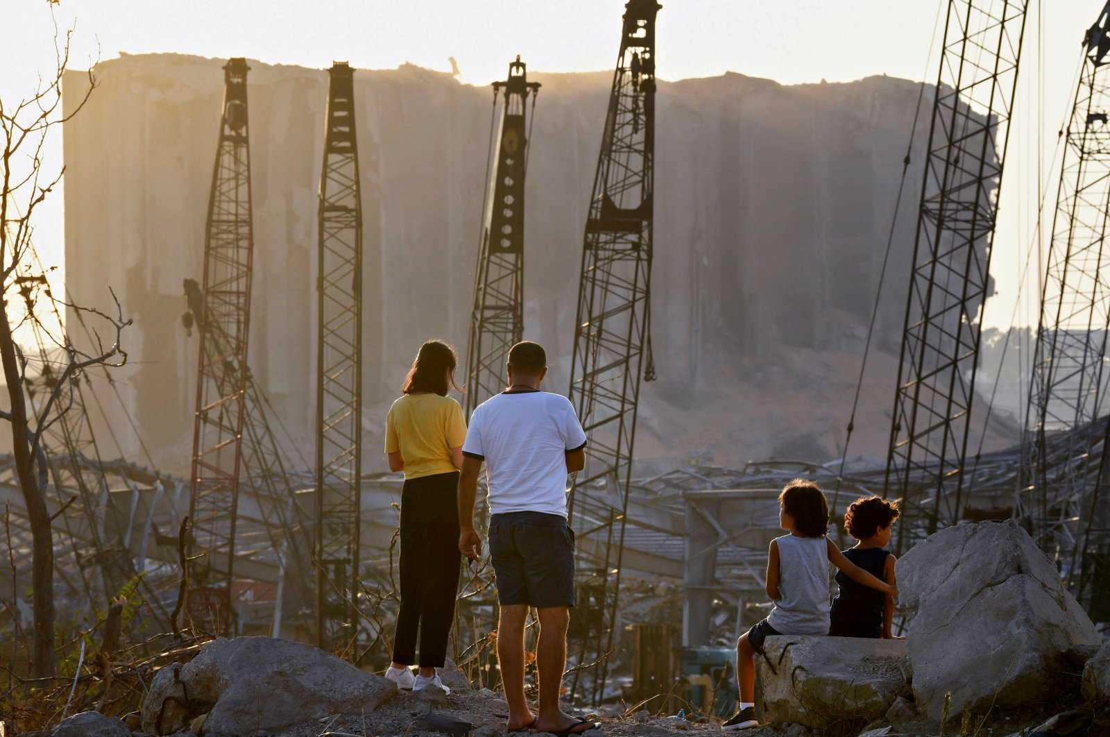 A couple and two children contemplate the damage in front of the grain silo at the port of Beirut, Aug.13, 2020. (AFP Photo)