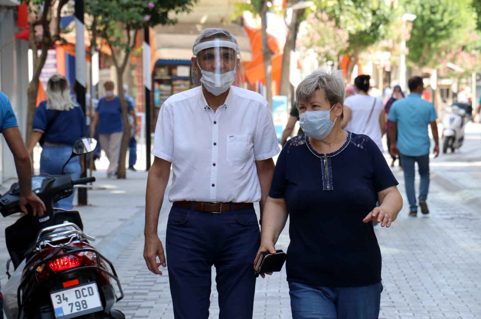 A man and a woman wearing protective masks walk on a street in Kırklareli, northwestern Turkey, Aug. 14, 2020. (AA Photo)