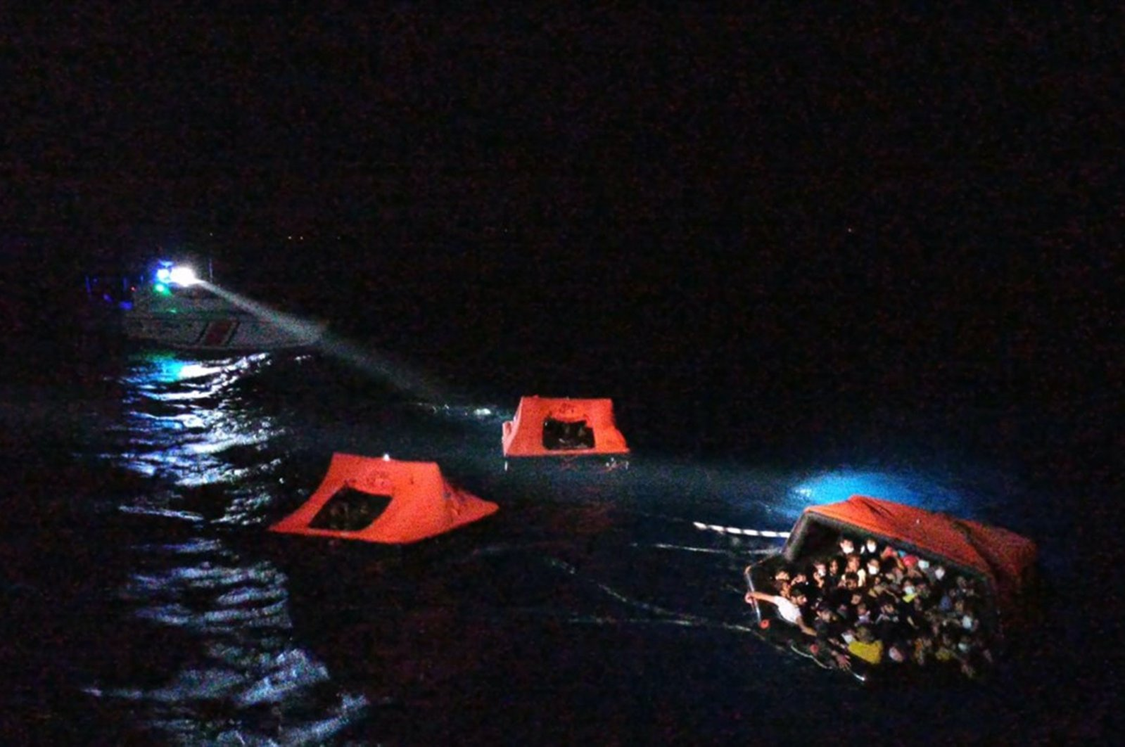 In this picture, 83 migrants who were pushed back by Greek coastal authorities into Turkish waters off the Aegean coast, can be seen being rescued by the Turkish Coast Guard, August 14, 2020. (IHA Photo)