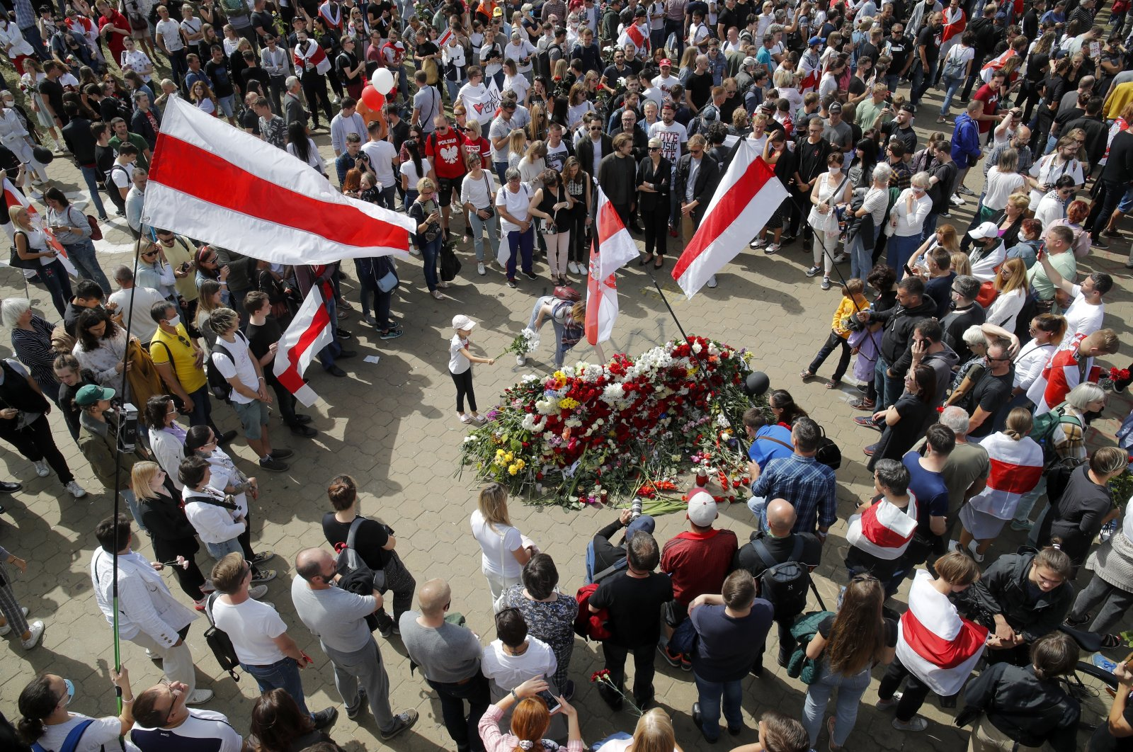 People with old Belarusian National flags lay flowers as they gather at the place where Alexander Taraikovsky died amid the clashes protesting the election results, during his civil funeral in Minsk, Belarus, Saturday, Aug. 15, 2020. (AP Photo)