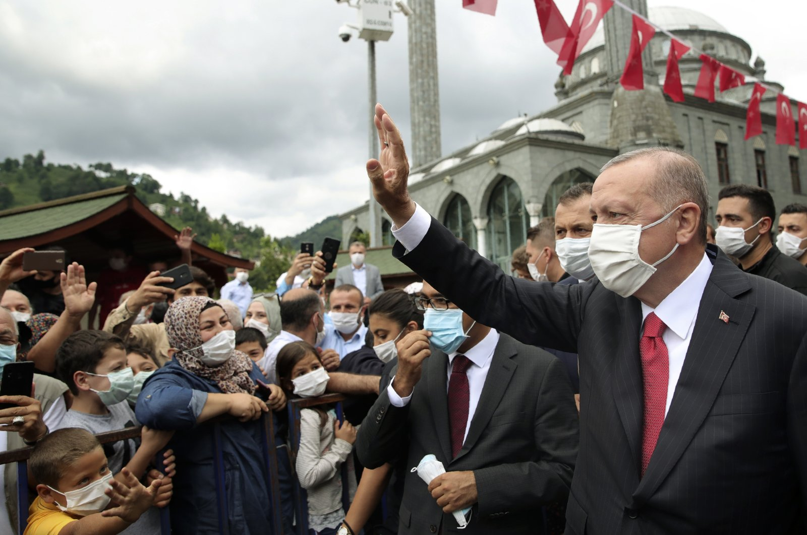 President Recep Tayyip Erdoğan wearing a face mask, as a precaution against the coronavirus, waves at his supporters in the Black Sea city of Rize, northern Turkey, Aug. 15, 2020. (AP Photo)
