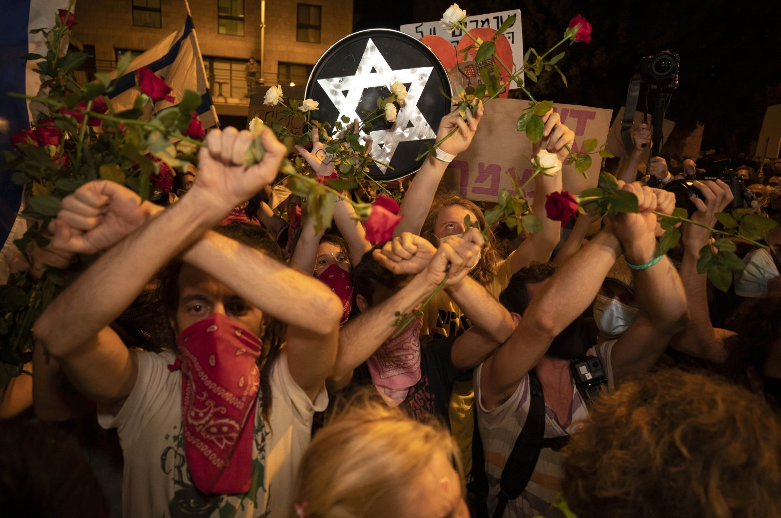 Israeli protesters hold flowers and chant slogans during a demonstration against Israeli Prime Minister Benjamin Netanyahu near the prime minister's residence in Jerusalem, Aug. 15, 2020. (AP Photo)