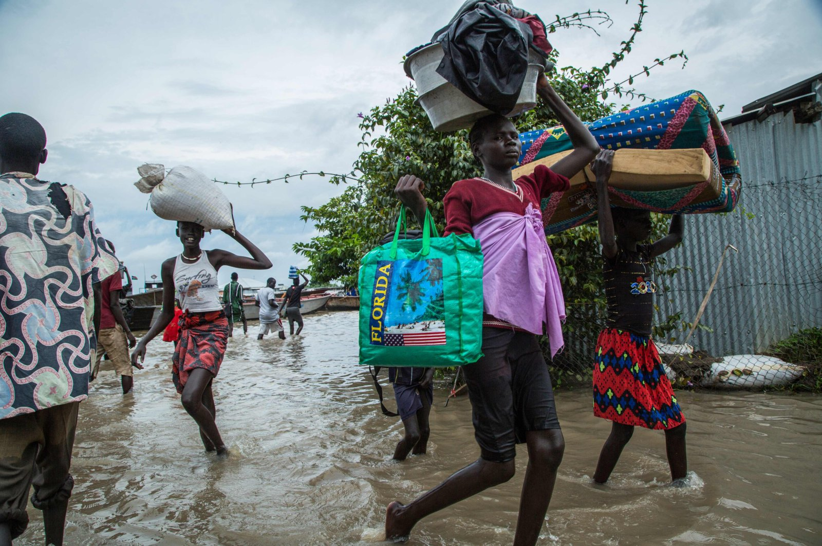 Displaced people walk with their belongings in a flooded area after the Nile river overflowed after continuous heavy rain which caused thousands of people to be displaced in Bor, central South Sudan, on Aug. 9, 2020. (AFP Photo)