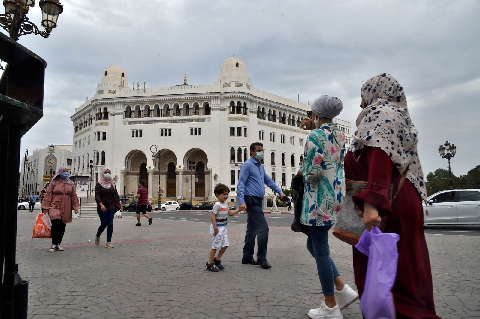 People wearing protective masks walk past the La Grande Poste (main post office) building in the center of the capital Algiers, Algeria, Aug. 12, 2020. (AFP Photo)