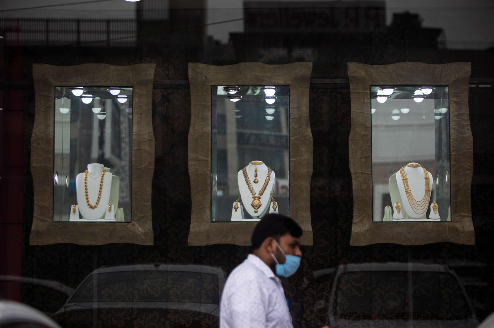 A man walks past a jewelry store window displaying gold necklaces in New Delhi, July 31, 2020. (AFP Photo)
