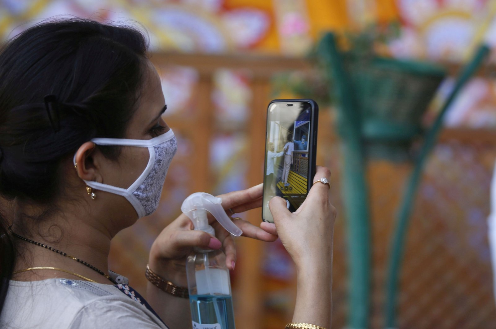 A woman takes a photograph with a cell phone as a paramedic conducts a rapid antigen test in Srinagar, the summer capital of Indian Kashmir, Aug. 10, 2020. (EPA Photo)