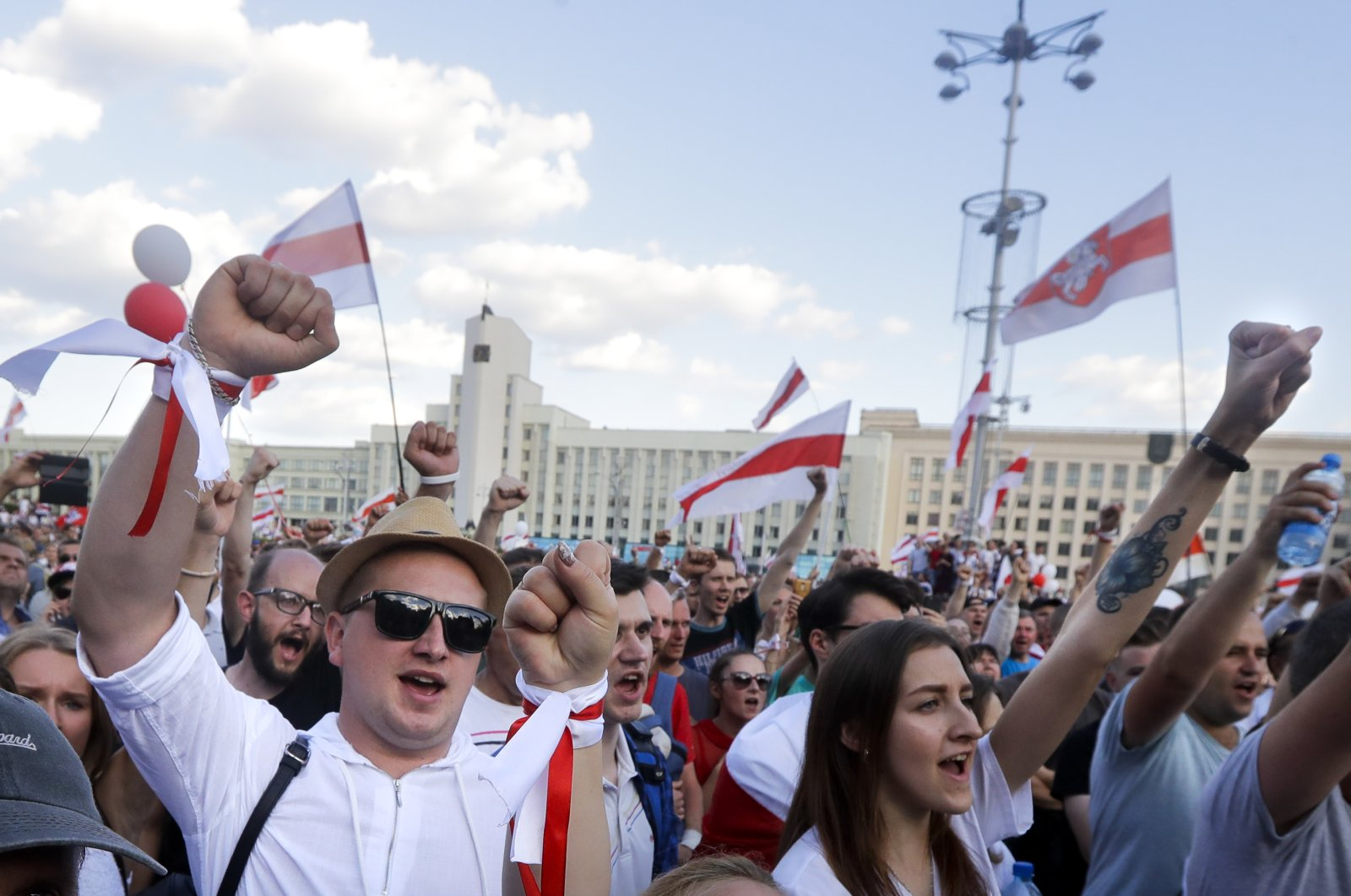People with old Belarusian national flags shout during an opposition rally in front of the House of Government building in Minsk, Belarus, Aug. 16, 2020. (AP Photo)