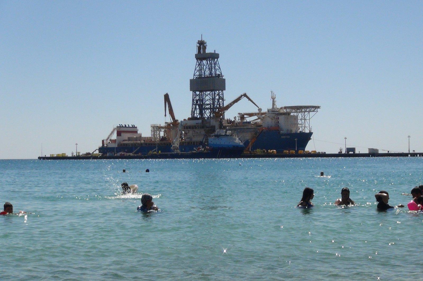 Vacationers swim near Turkey's third drillship Kanuni off Turkey's southern Mersin province, Aug. 17, 2020. (IHA Photo)
