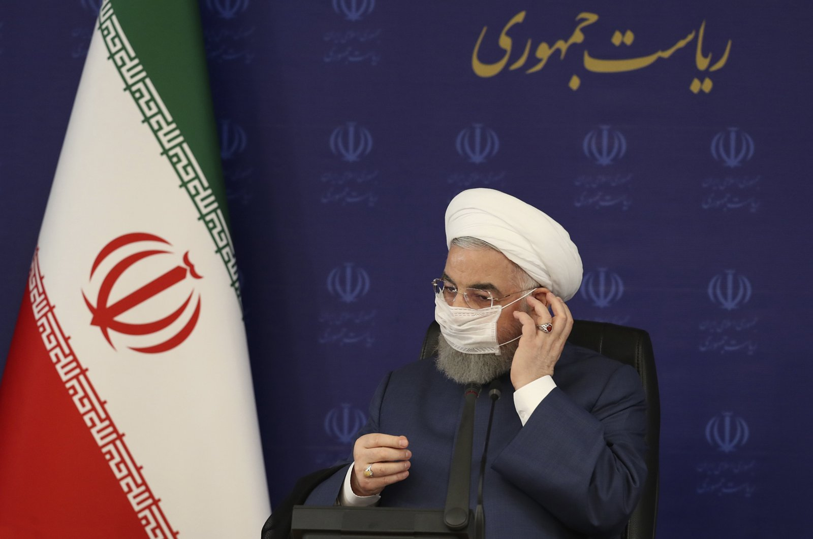 Iranian President Hassan Rouhani adjusts his face mask, Tehran, July 18, 2020. (AP Photo)
