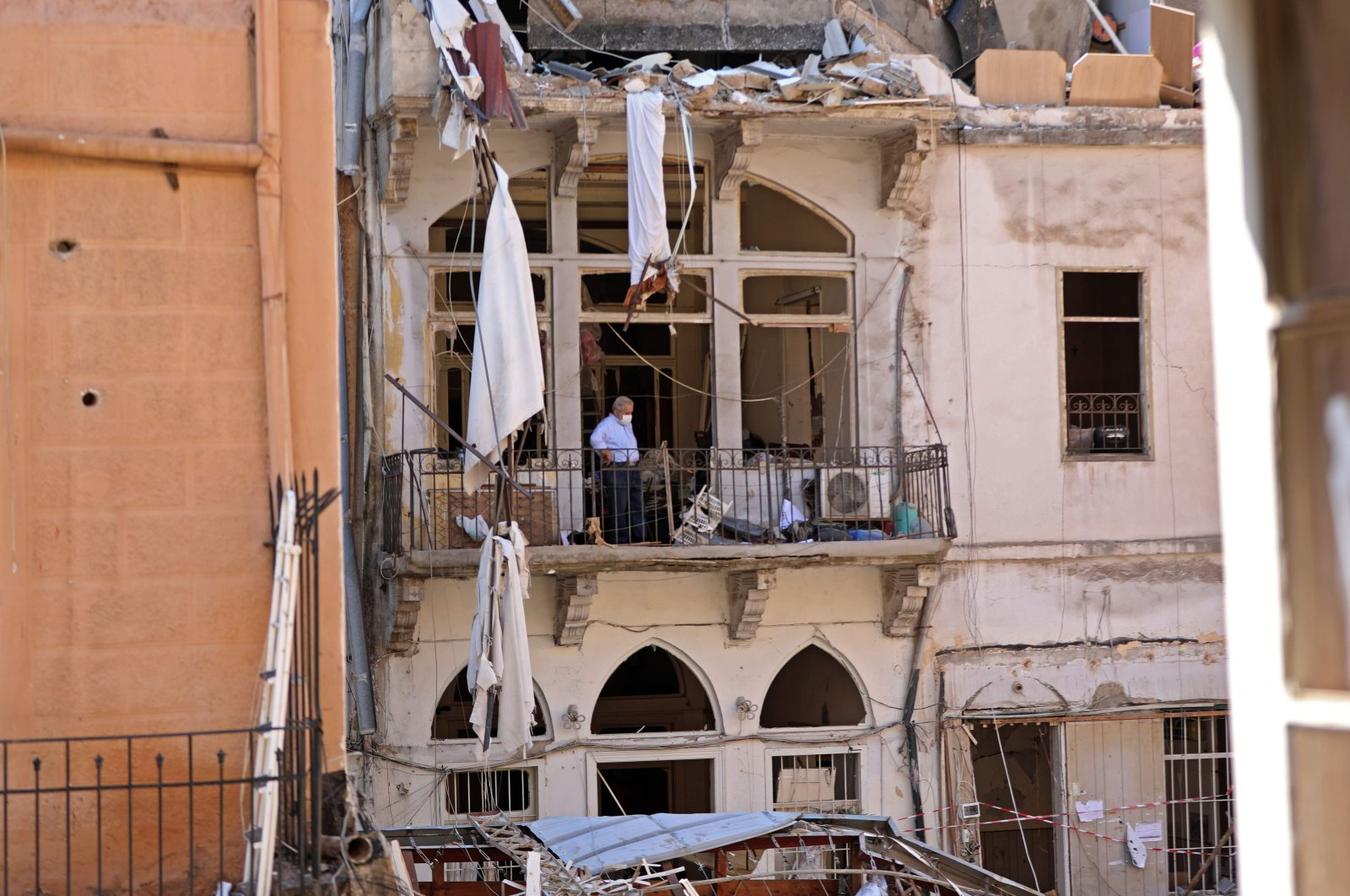 A man, clad in a mask due to the COVID-19 pandemic, stands amid debris on a balcony in the partially destroyed neighborhood of Mar Mikhael, Beirut, Lebanon, Aug. 14, 2020. (AFP Photo)