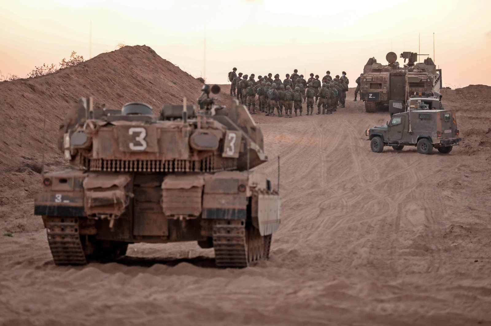 Israeli infantry soldiers gather next to tanks and an armored personnel carrier near the Israeli border with the Gaza Strip, Aug. 16, 2020. (AFP Photo)